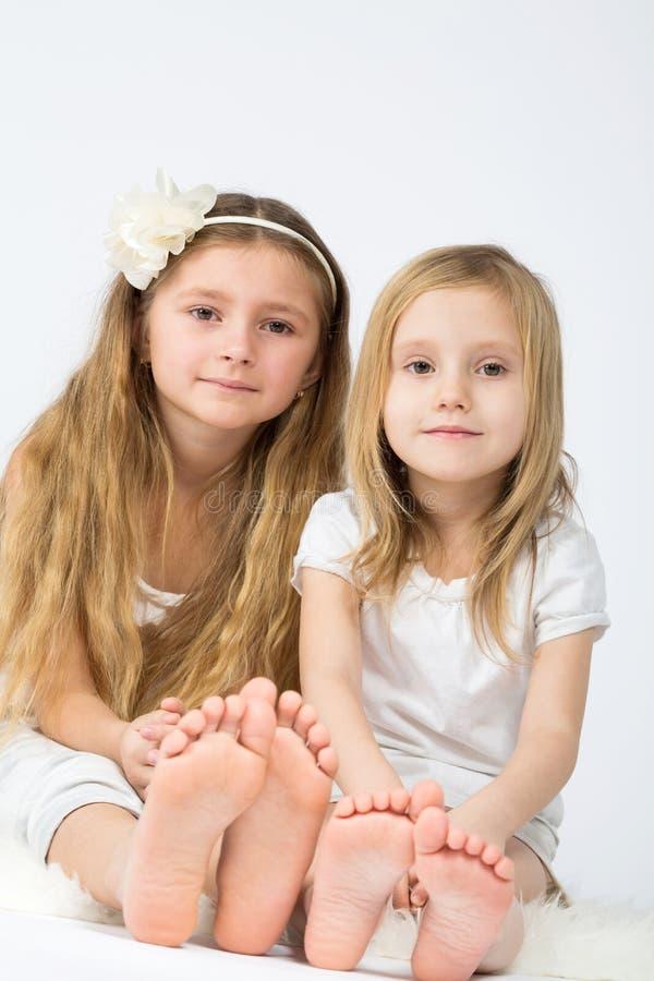 Dwa małej dziewczynki ubierającej w białym obsiadaniu fotografia stock