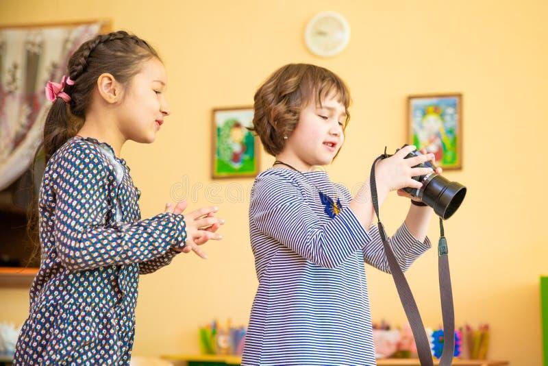 Dwa małej dziewczynki uczy się dlaczego używać fotografii kamerę zdjęcie royalty free