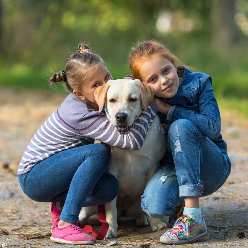 Dwa małej dziewczynki z psem Miłość fotografia royalty free