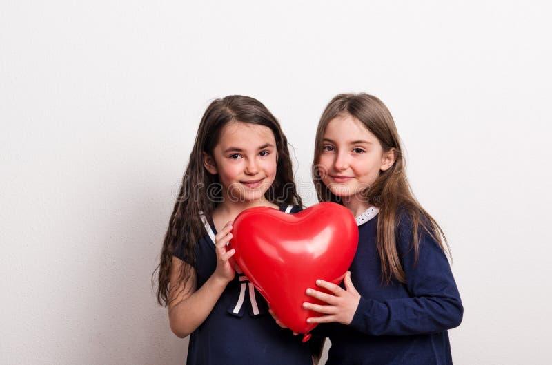 Dwa małej dziewczyny w studiu, trzyma czerwonego serce balon przed one zdjęcia stock