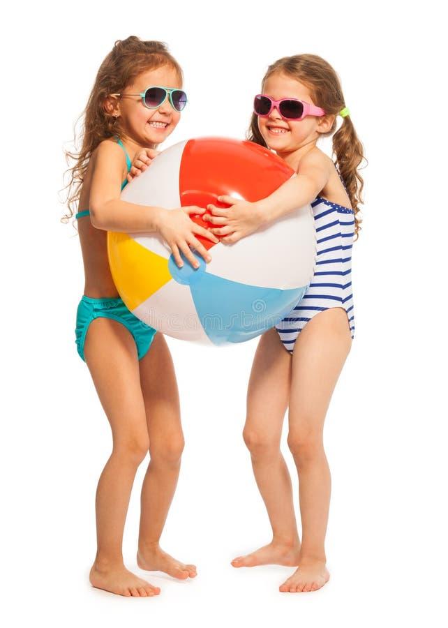 Dwa małej pływaczki łapie dużą piłkę zdjęcie stock