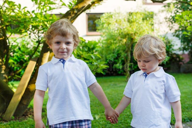 Dwa małej rodzeństwo chłopiec ma zabawę w rodzinnym spojrzeniu outdoors zdjęcia stock