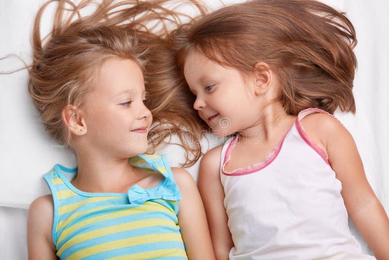 Dwa małej siostry śpią wpólnie, spojrzenie z pozytywnymi wyrażeniami przy each inny, ubierają w przypadkowych ubraniach, dobrych  obrazy royalty free