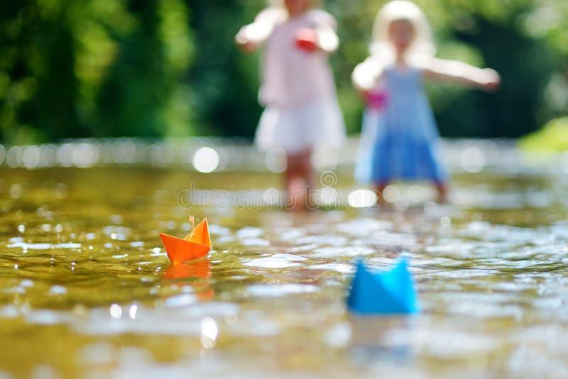 Dwa małej siostry bawić się z papierowymi łodziami fotografia stock