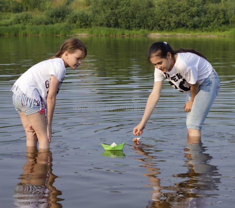 Dwa małej siostry bawić się z papierowymi łodziami rzeką dalej grżą a fotografia royalty free