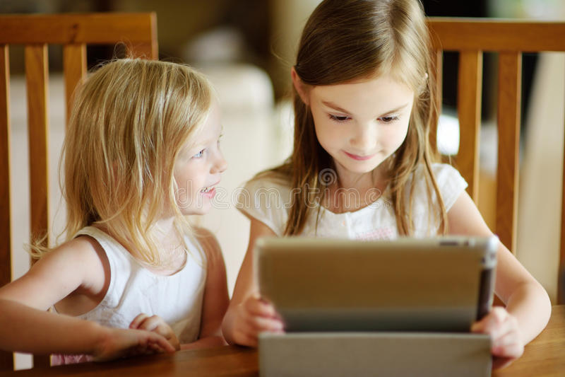 Dwa małej siostry używa cyfrowego pastylka komputer zdjęcie stock