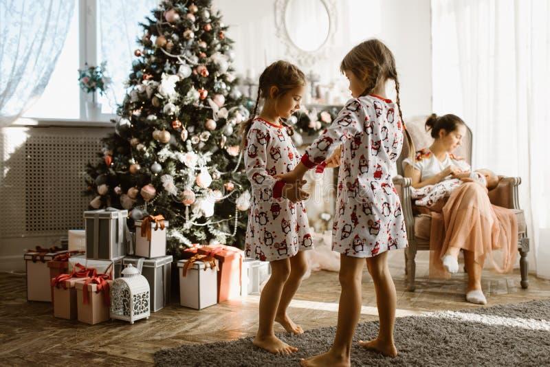 Dwa małej siostry w piżamach ma zabawa nowego roku drzewa z gi obraz royalty free