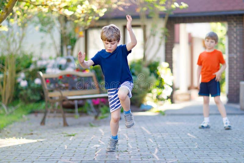 Dwa małej szkoły i preschool dzieciaków chłopiec bawić się hopscotch na boisku fotografia royalty free