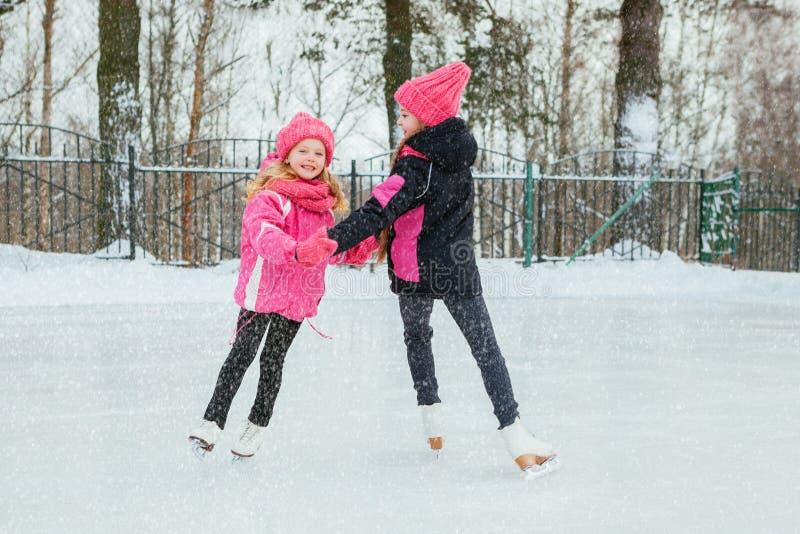 Dwa Małej uśmiechniętej dziewczyny jeździć na łyżwach na lodzie w menchiach są ubranym i ręcznie robiony szaliki plenerowy Zima zdjęcie royalty free