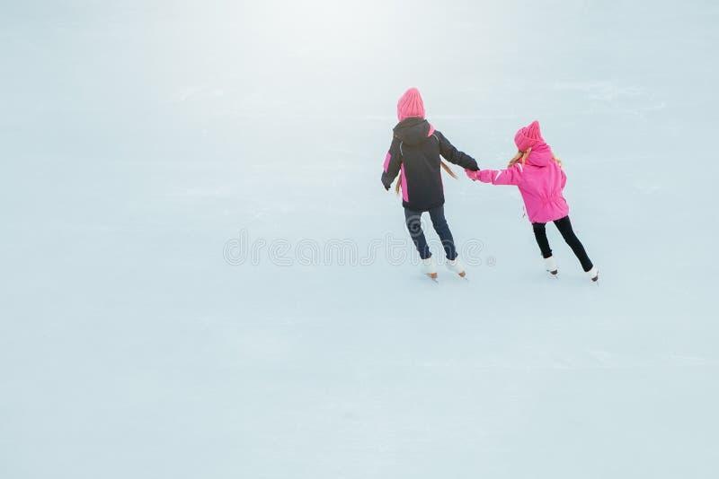 Dwa Małej uśmiechniętej dziewczyny jeździć na łyżwach na lodzie w menchiach są ubranym i ręcznie robiony szaliki plenerowy Zima obraz royalty free