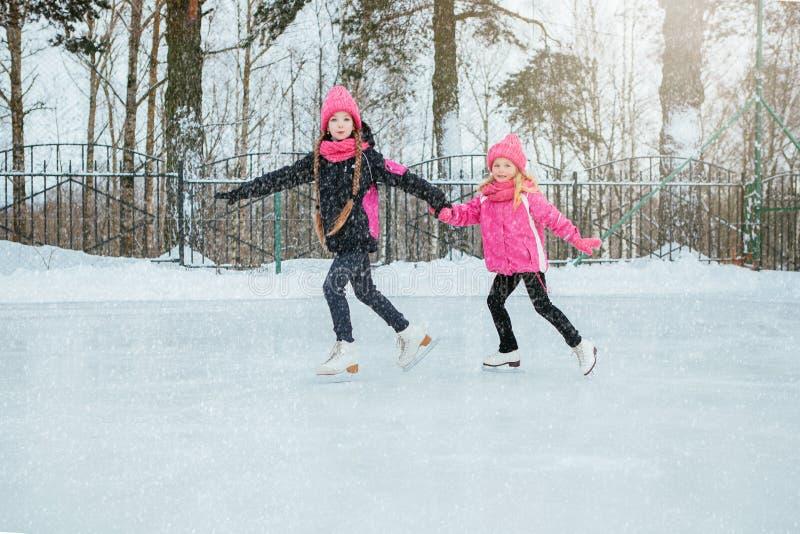 Dwa Małej uśmiechniętej dziewczyny jeździć na łyżwach na lodzie w menchiach są ubranym i ręcznie robiony szaliki plenerowy Zima zdjęcia stock