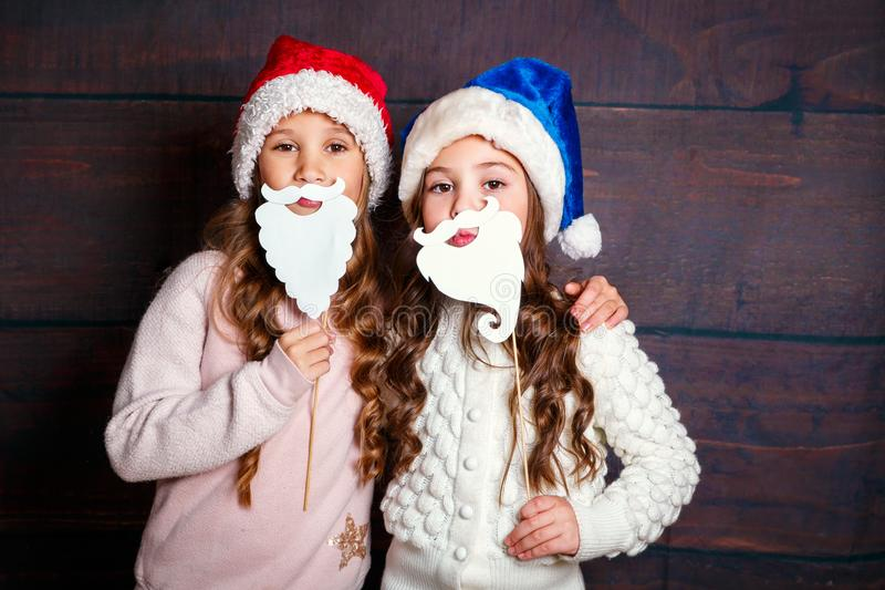 Dwa małej uśmiechniętej dziewczyny ma zabawę Bożenarodzeniowy pojęcie Uśmiechnięte śmieszne siostry w Santa kapeluszu na drewnian obraz stock
