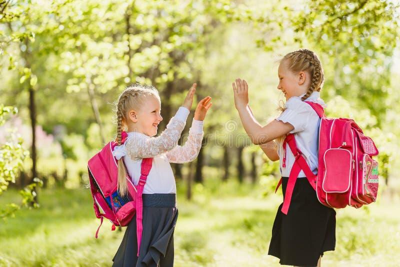 Dwa małych dziewczynek uczennica z różowym plecakiem outdoors i sztuka tortem zdjęcia royalty free