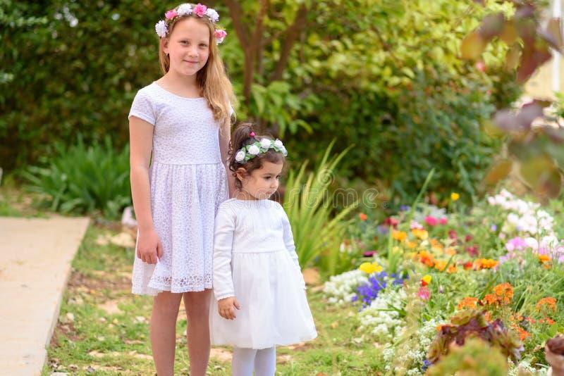 Dwa ma?ej dziewczynki w bia?ych sukniach i kwiatu wianku ma zabaw? lato ogr?d obrazy royalty free