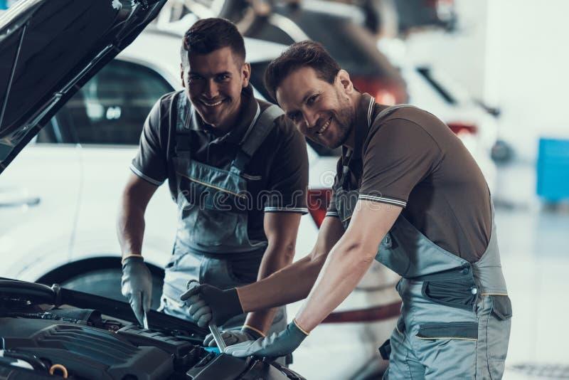 Dwa Mecanics Patrzeje kamerę podczas gdy Załatwiający samochód obrazy stock