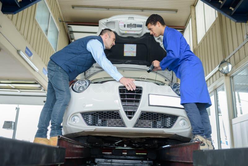 Dwa mechanika pracuje na samochodowym silniku przy garażem zdjęcia stock