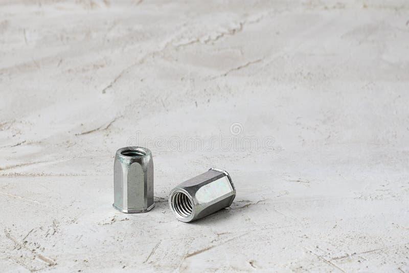 Dwa metal popielatej rzecznej dokrętki dla ciężkiej wewnętrznej nici dla cienkich jednostek na lewej części ściągły horyzontalny  zdjęcie royalty free