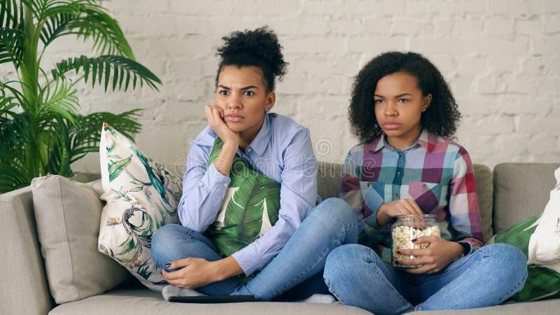 Dwa mieszającego biegowego kędzierzawego dziewczyna przyjaciela siedzi na leżanki i zegarka dreszczowa filmu i jedzą popkorn w do zdjęcie stock