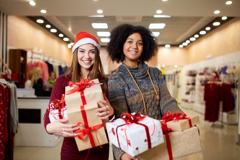 Dwa mieszającej biegowej kobiety z prezentów pudełkami w rękach przy sklepem Wielo- etniczne dziewczyny ono uśmiecha się z teraźn zdjęcia royalty free