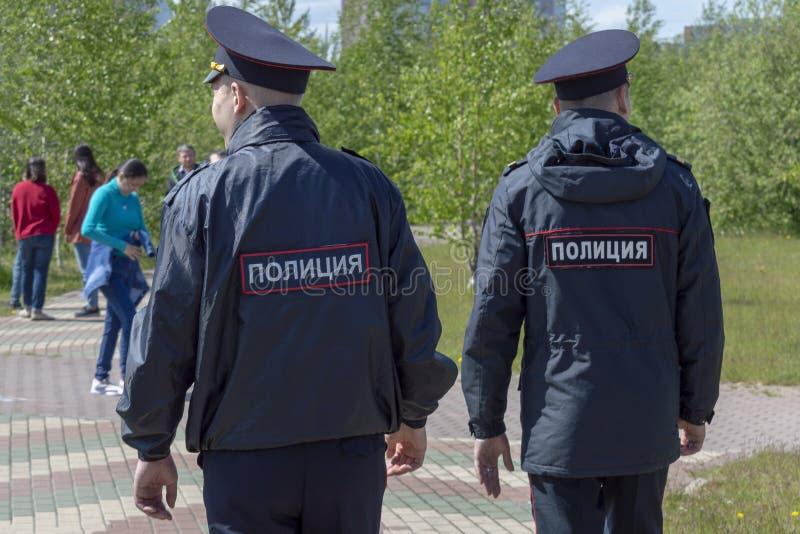 Dwa milicyjnego mężczyzny w mundurze iść miejsce dokąd wakacyjny, tylni widok, fotografia stock