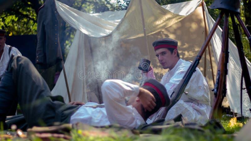 Dwa militarnego ludzie odpoczywa na ziemi obrazy stock