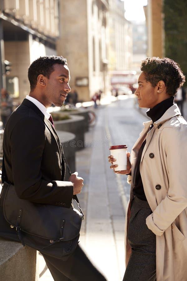 Dwa millennial coworkers stoi na pogodnej ulicie w mieście opowiada, trzy ćwiartek długość, pionowo zdjęcia stock