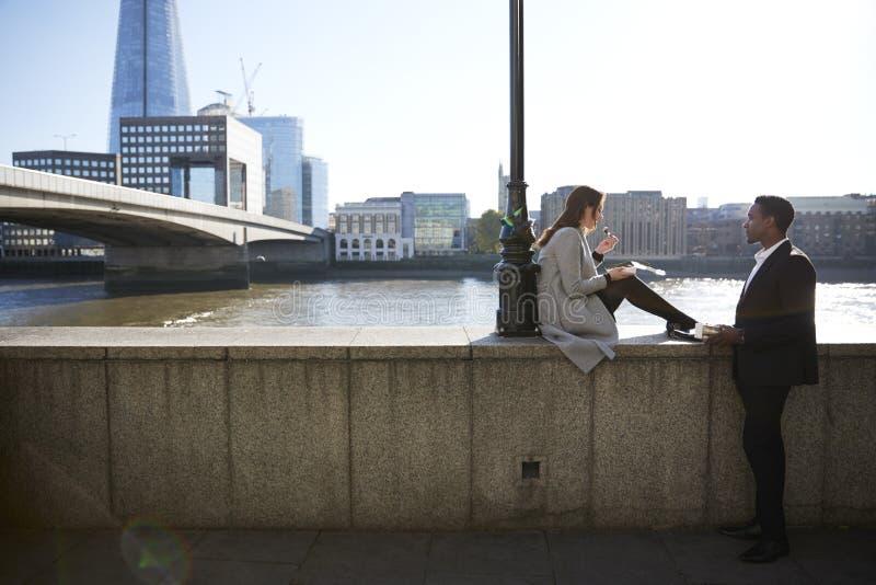 Dwa millennial kolegi biorą przerwy obsiadanie na bulwaru łasowaniu blisko Londyn mostu Rzecznym Thames, backlit obrazy stock