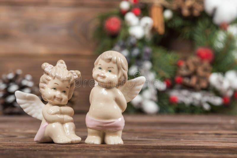 Dwa mini postaci dziewczyna i chłopiec aniołowie - dekoracje świąteczne ekologicznego drewna wianek Bożenarodzeniowa zimy rama na zdjęcie royalty free