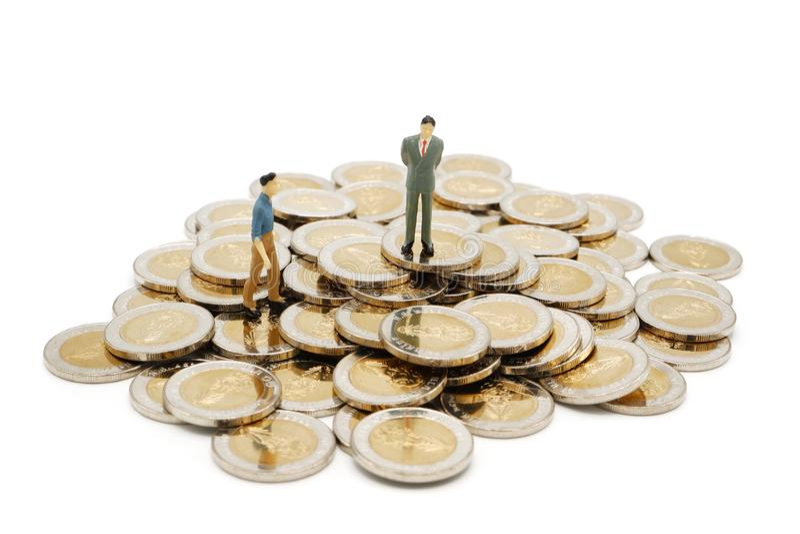 Dwa miniaturowego ludzie chodzi i stoi na stosie nowe 10 Tajlandzkiego bahtu monet zdjęcie royalty free