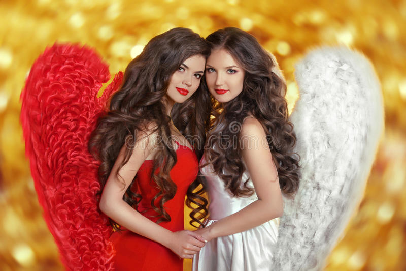Dwa moda aniołów Pięknej dziewczyny modelują z kędzierzawy długie włosy fotografia royalty free