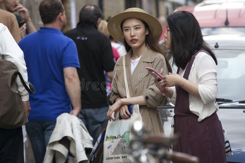 Dwa modnej pięknej Japońskiej dziewczyny Wielki pstrobarwny tłum chodzi w górę Brickline na Niedziela popołudniu Pchli targ na Br zdjęcie stock