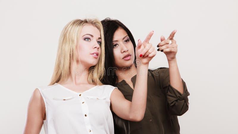 Dwa mody kobiety wskazuje dowcipu palec fotografia stock