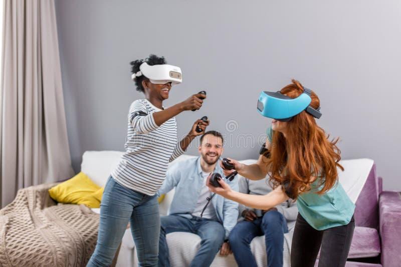 Dwa multiracial młodej kobiety tanczy będący ubranym rzeczywistość wirtualna szkła indoors zdjęcie royalty free