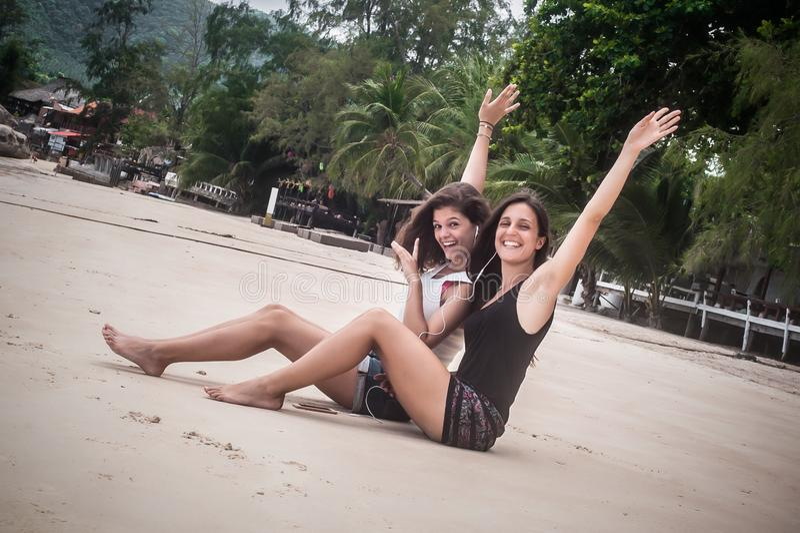 Dwa najlepszego przyjaciela słucha muzykę na smartphone, cieszy się na plaży obraz royalty free