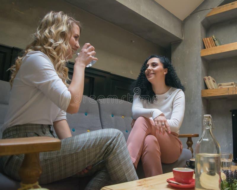 Dwa najlepszy dziewczyny są opowiadający i gawędzący przy kawiarnią zdjęcie stock