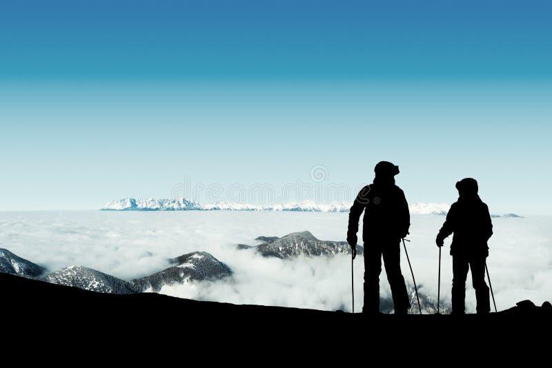 Dwa narciarki dostaje czytelniczego przygotowywający dla zjazdowej przejażdżki z wierzchu góry zdjęcie royalty free