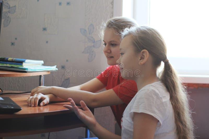 Dwa nastolatek dziewczyny - szczęśliwa kobieta blisko stołu z komputerem osobistym w domu fotografia royalty free