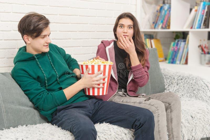 Dwa nastolatka ogląda TV siedzą na leżance fotografia royalty free