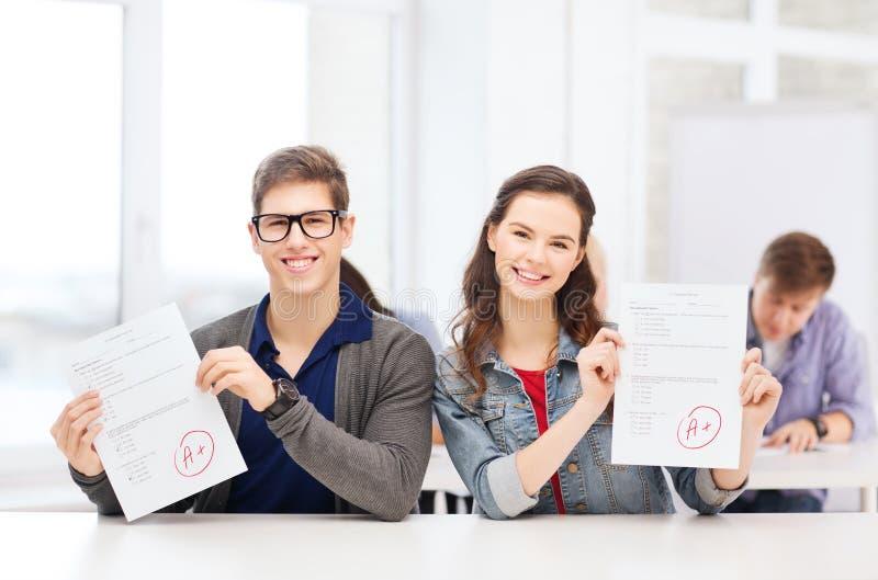Dwa nastolatka trzyma test lub egzamin z stopniem A obraz royalty free