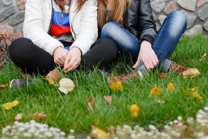 Dwa nastoletnia dziewczyna przyjaciela siedzi na zielonej trawie zdjęcie stock