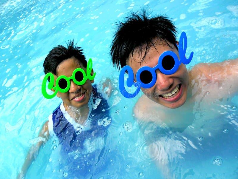 Dwa nastoletniego chłopaka jest ubranym okulary przeciwsłonecznych z słowem cool dla swój ramy w pływackim basenie zdjęcia royalty free