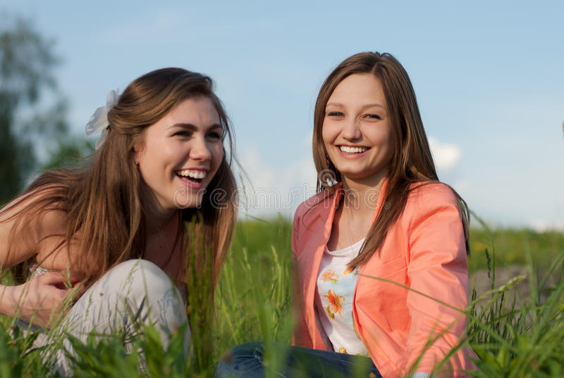 Dwa Nastoletniego dziewczyna przyjaciela Śmia się w zielonej trawie obrazy royalty free