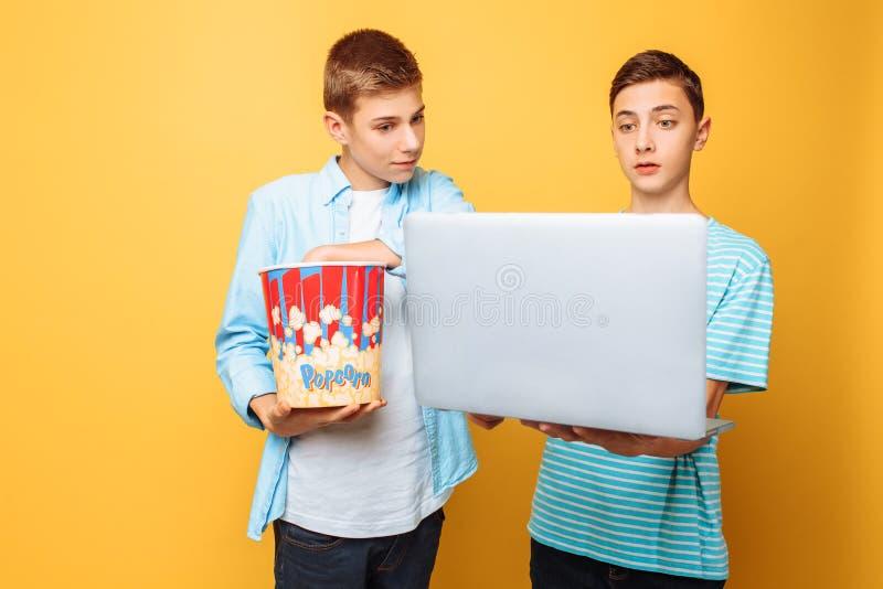Dwa nastoletniego przyjaciela z wiadrem popkorn w ich rękach i laptopu narządzaniu oglądać filmy na żółtym tle zdjęcia royalty free