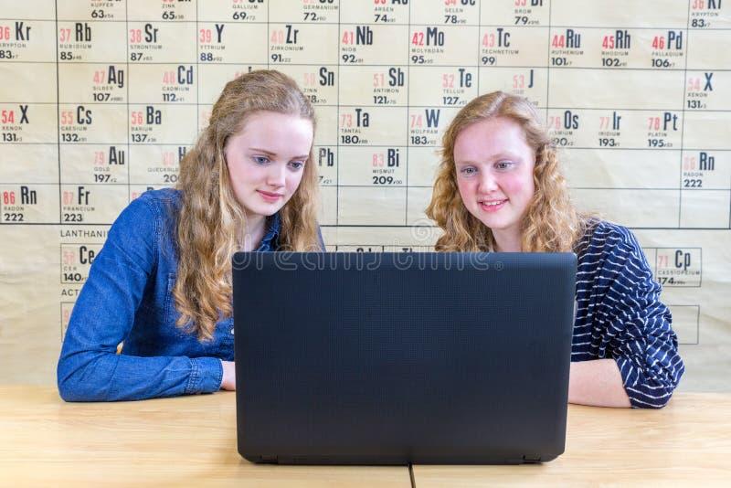Dwa nastoletniej dziewczyny patrzeje komputer w chemii lekci fotografia royalty free