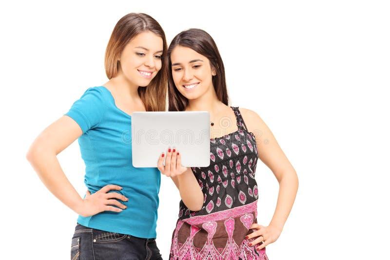 Dwa nastoletniej dziewczyny patrzeje pastylkę zdjęcia stock