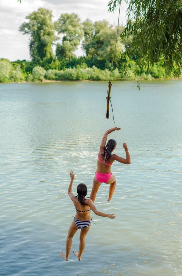 Dwa nastoletniej dziewczyny skacze w rzekę obrazy stock