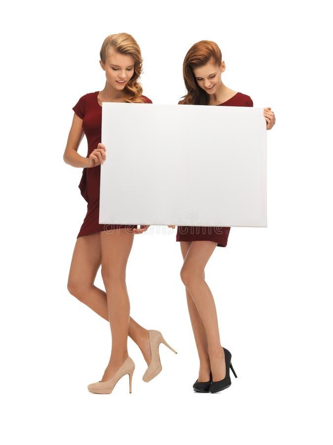 Dwa nastoletniej dziewczyny w czerwonych sukniach z puste miejsce deską fotografia royalty free