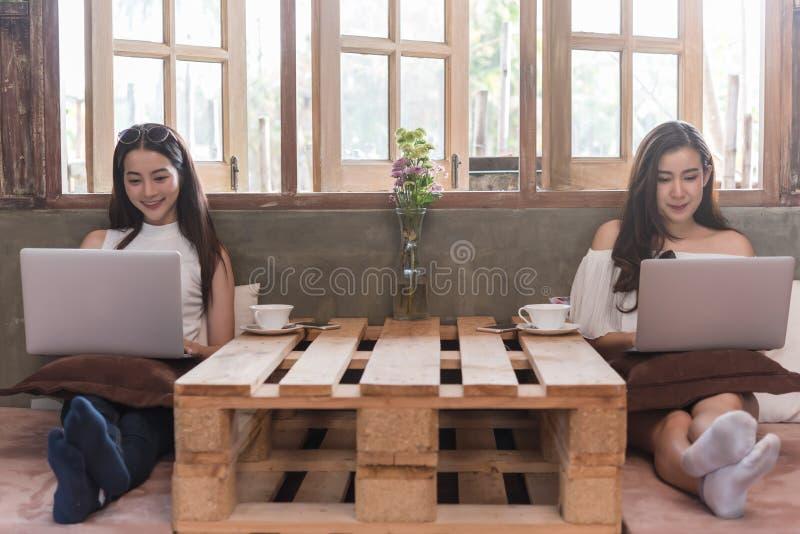 Dwa nastoletniej kobiety spotykaj? w sklep z kaw? use laptopie i smartphone obraz royalty free
