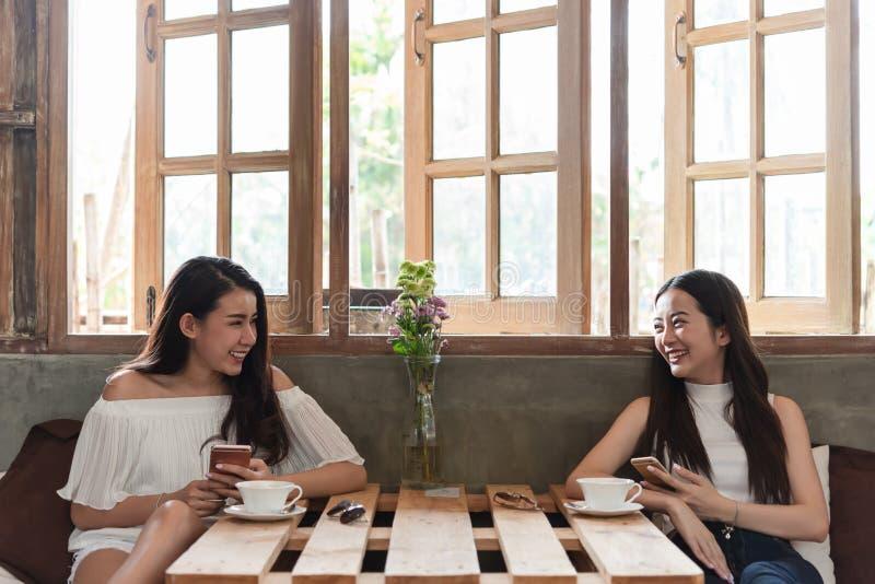 Dwa nastoletniej kobiety spotykaj? w sklep z kaw? use smartphone sztuki socjalny fotografia royalty free