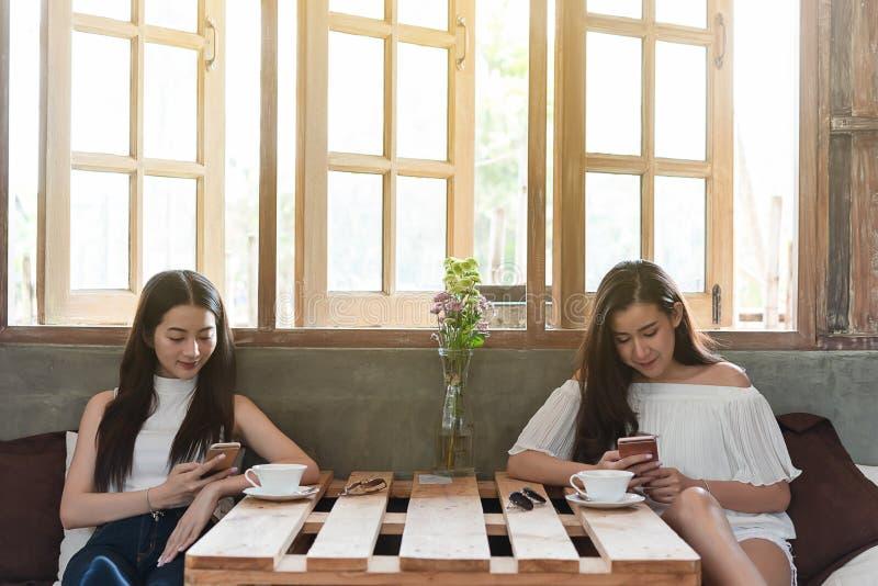 Dwa nastoletniej kobiety spotykaj? w sklep z kaw? use smartphone sztuki socjalny zdjęcia stock